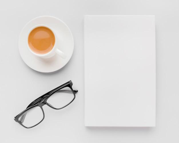 Tazza di caffè e bicchieri accanto al libro