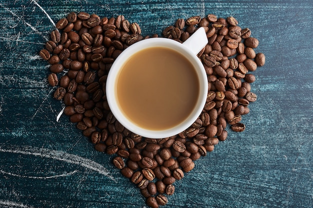 A cup of coffee on grains in heart shape.