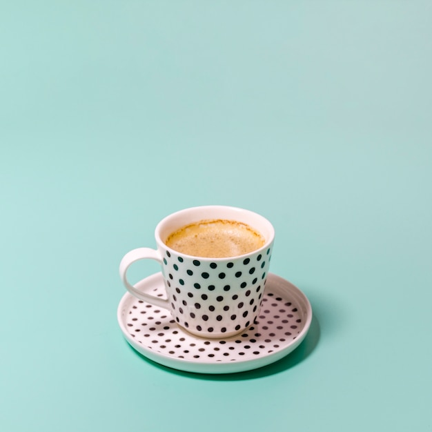 Cup of coffee on green background