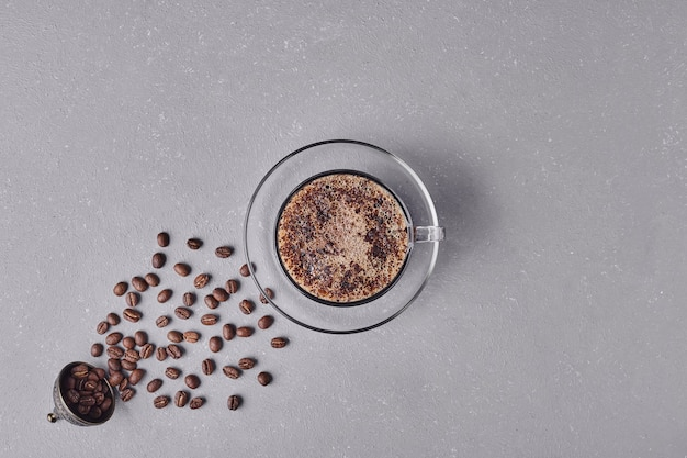 A cup of coffee on grey background.