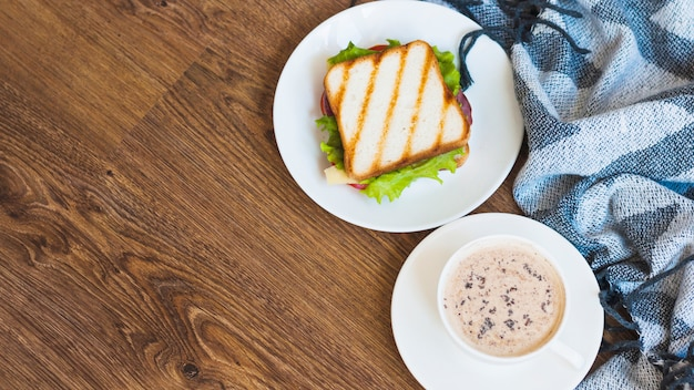 Cup of coffee and grilled sandwich with napkin on wooden table