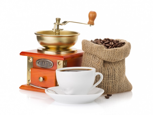 Cup of coffee, grinder and beans on white