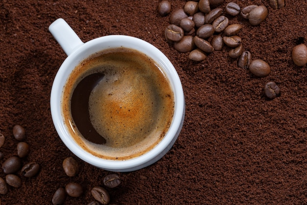 Cup of coffee on ground coffee. closeup.