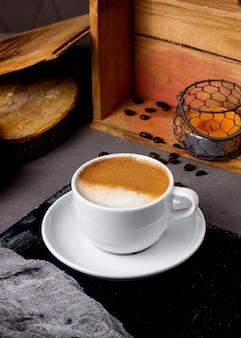 Una tazza di caffè decorata a metà con granelli di caffè