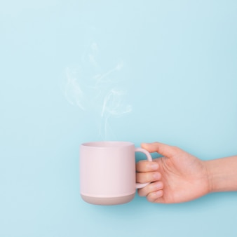 Cup of coffee in the hand on blue background