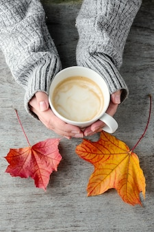 A cup of coffee in hands and autumn leaves on a wooden table