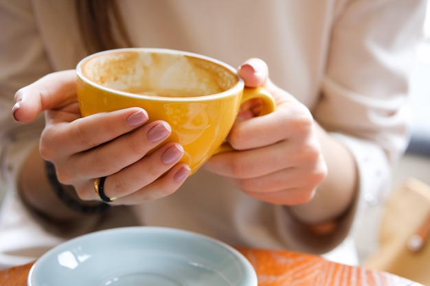 A cup of coffee in the hands of a young woman. coffee break, breakfast.
