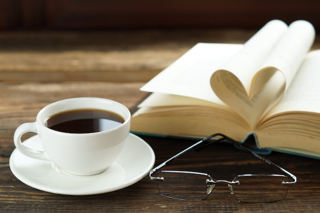 A cup of coffee and heart book with glasses on wooden table