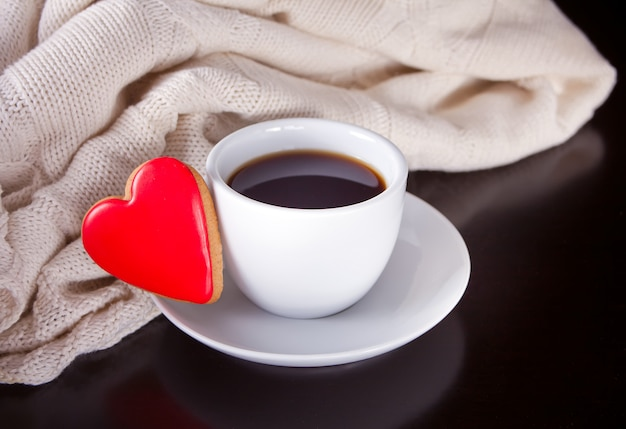 Cup of coffee and heart shaped cookie on the wooden table