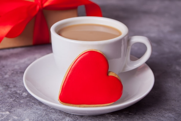 Cup of coffee and a heart shaped red cookie with gift box on the background.