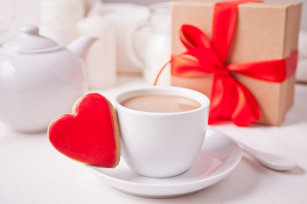 Cup of coffee and a heart shaped red cookie with gift box and teapot on the white table