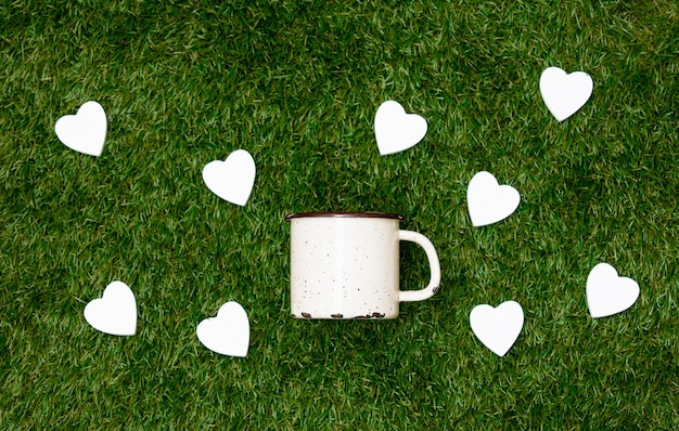 Cup of coffee and heart shapes on green grass.
