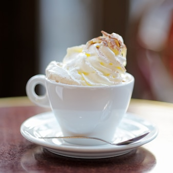 Cup of coffee or hot chocolate with whipped cream on the table at the cafe