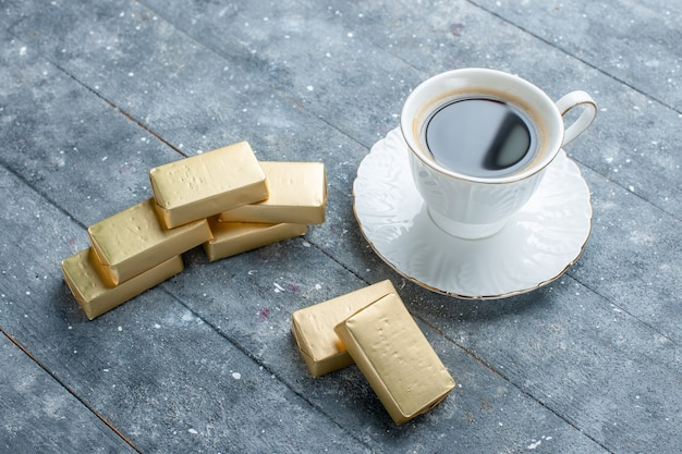 Cup of coffee hot and strong with gold formed chocolate on blue desk, coffee cocoa drink hot