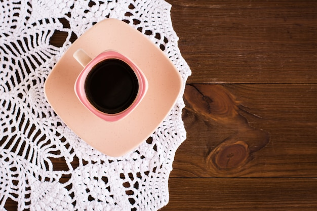 The  cup  of coffee is on knitted openwork napkin on wood table. top view