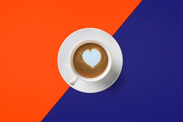 Cup of coffee isolated on orange and blue