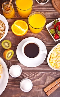 Cup of coffee, juice eggs, fruits and toasts. breakfast concept