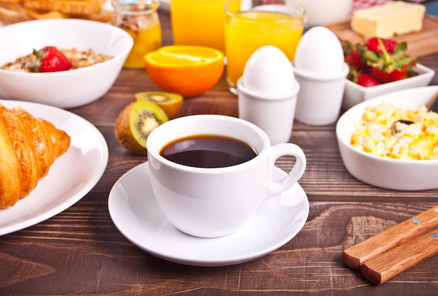 Cup of coffee, juice, eggs, fruits, toasts. breakfast concept.