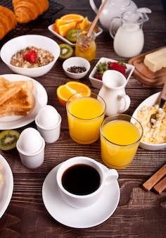 Cup of coffee, juice eggs, fruits and toasts