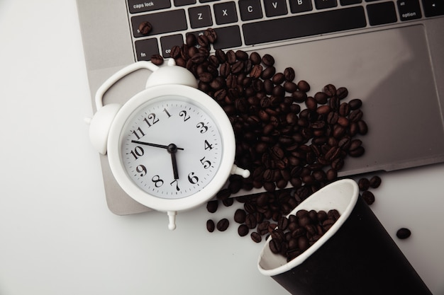 A cup of coffee on keyboard, white alarm clock and coffee beans. morning workplace concept.