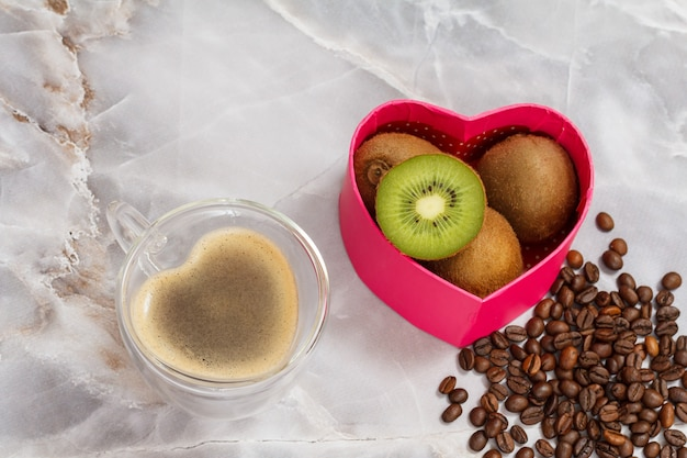 Cup of coffee, kiwi fruits and roasted coffee beans on kitchen desk.