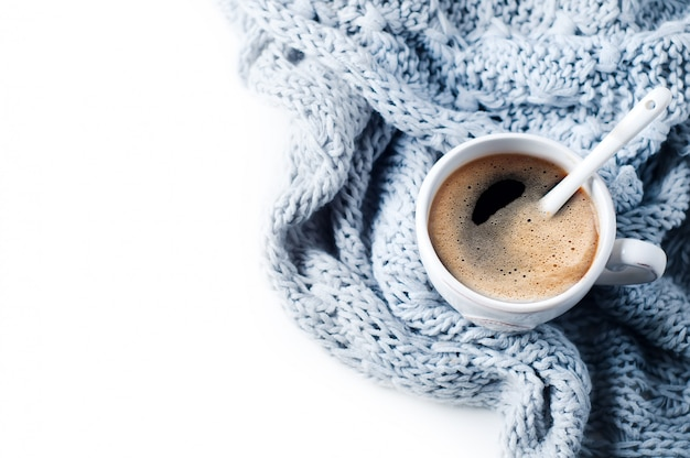 Cup of coffee and knitted sweater on the white table