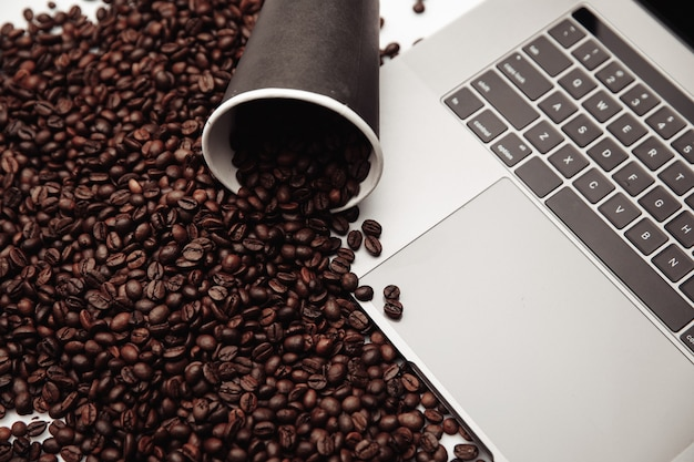 A cup of coffee on laptop and coffee beans.