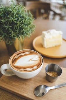 A cup of coffee latte art in coffee shop cafe on wood board with a piece of cake