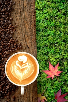Cup of coffee latte and coffee bean on old bark with three of colorful maple