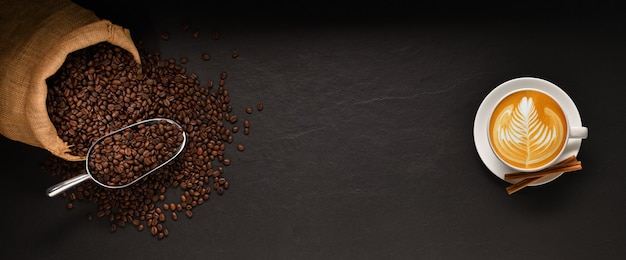 Cup of coffee latte and coffee beans in burlap sack on black background