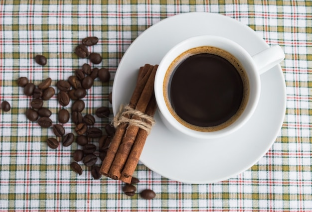 A cup of coffee on light background with cinnamon and coffee beans. top view