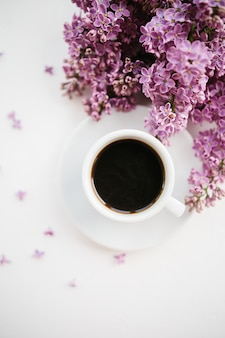 Cup of coffee and lilac branch on white