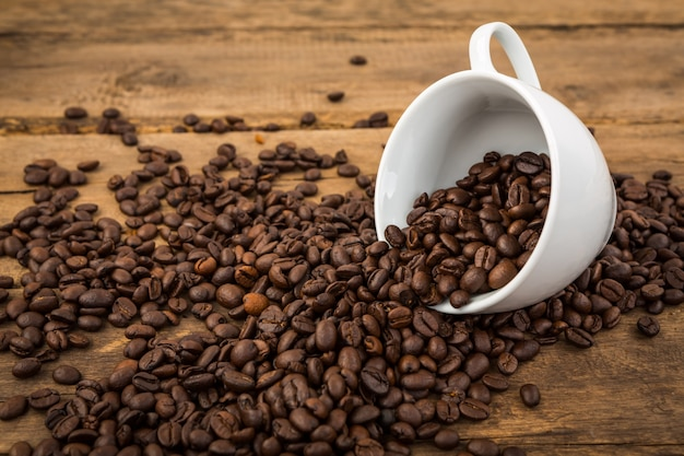 Cup of coffee lying down with coffee beans coming out of it
