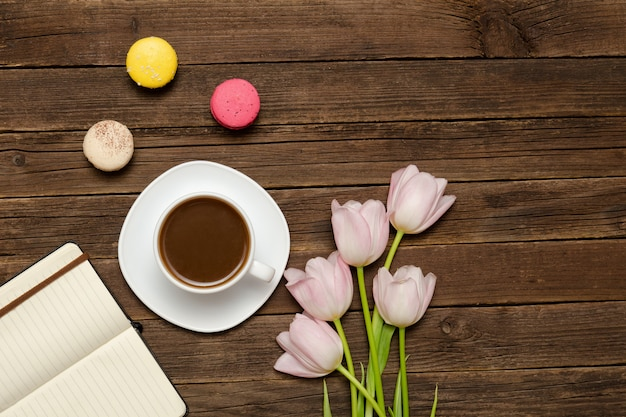 Cup of coffee, macarons, pink tulips and notebook on wooden background. top view