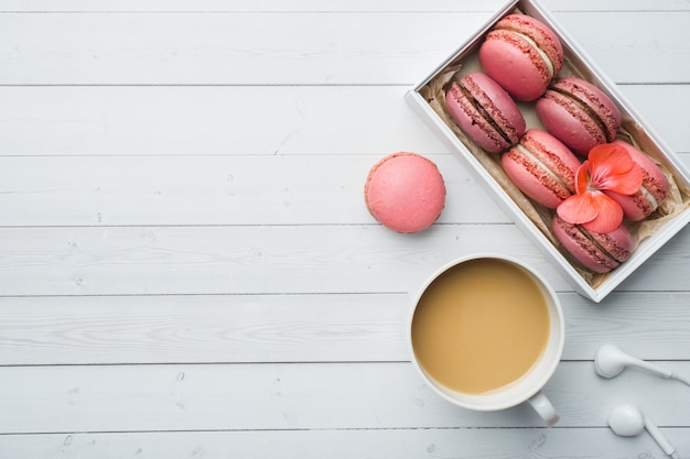 Cup of coffee, macaroon cookies in a box, flowers on a white background with copy space