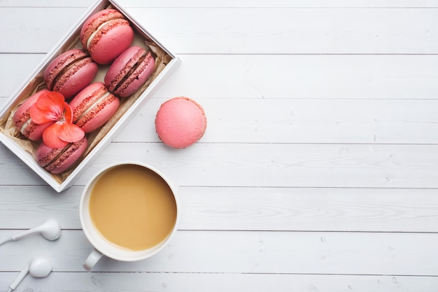 Cup of coffee, macaroon cookies in a box, flowers on a white table. copy space. concept beautiful breakfast. flat lay