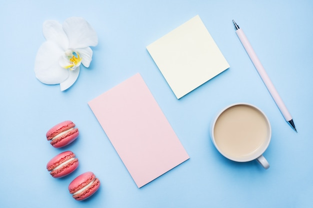 Cup of coffee, macaroon cookies and notepad with flat lay