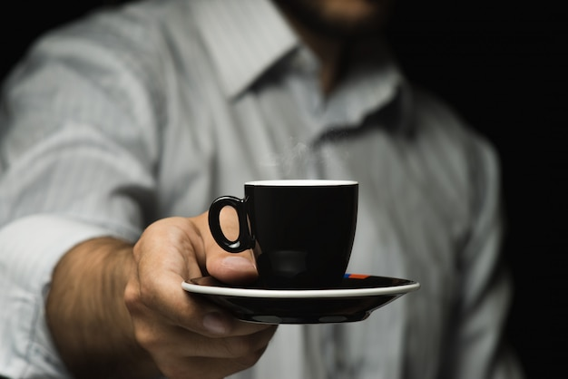 Cup of coffee in a man's hand.