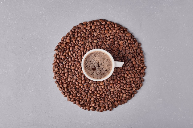 A cup of coffee in the mildde of arabica beans.