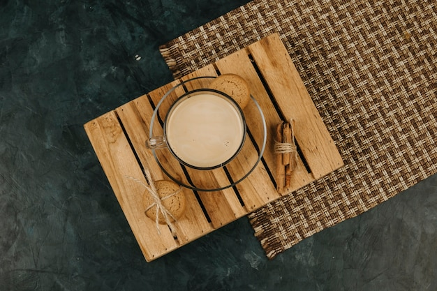 A cup of coffee milk on the wooden table in the dark blue background