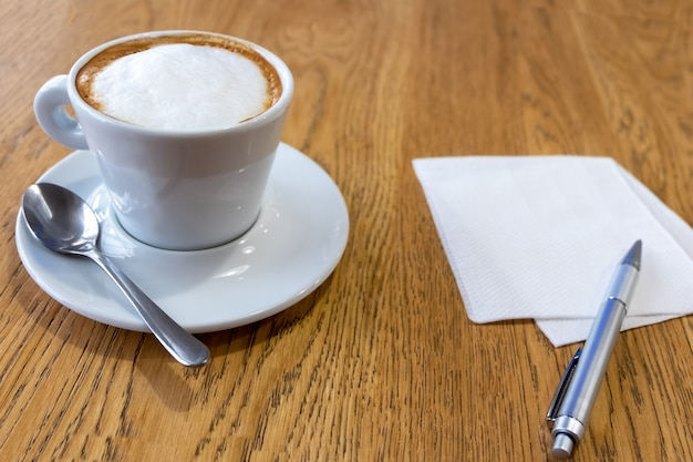 A cup of coffee and a napkin for a message on a wooden table