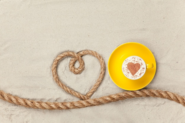 Cup of coffee near heart shape rope on sand surface