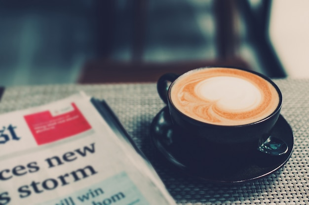 A cup of coffee and a newspaper of coffee on a wooden table