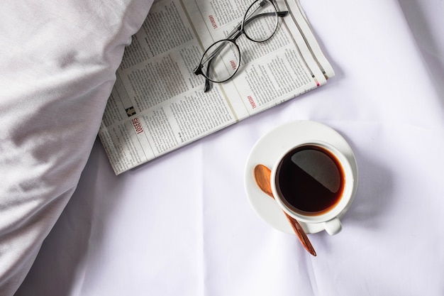 A cup of coffee and a newspaper on a white bed in the morning.