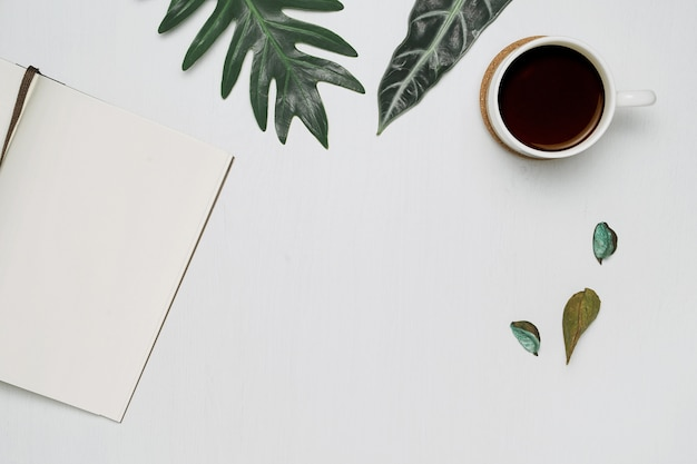 Cup of coffee and notebook on white wooden background with tropical monstera leaves