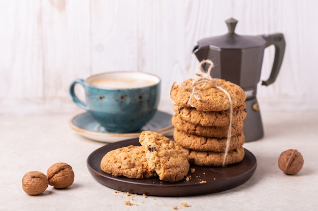 Cup of coffee, oatmeal cookies, coffee maker on white wooden background.