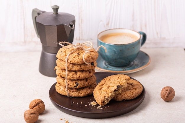 Cup of coffee, oatmeal cookies, coffee maker