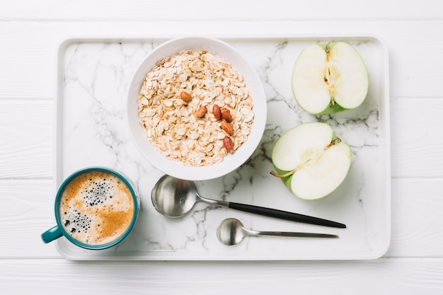 Cup of coffee; oatmeal and halved apple with spoons on tray over table