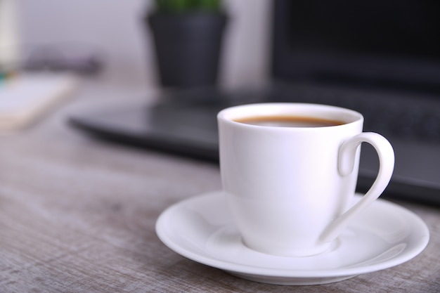 Cup of coffee on office desktop with laptop, computer on wooden table. close up