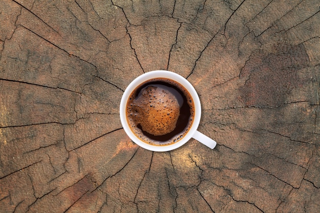 A cup of coffee on old tree stump texture background